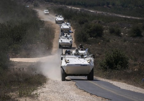 Members of the UNDOF ride armoured personnel carriers in the Israeli-occupied Golan Heights before crossing into Syria