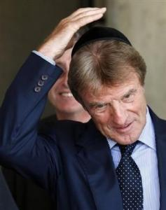 French Foreign Minister Bernard Kouchner takes off a Jewish skull-cap, or Kippa, at the end of a visit to the Yad Vashem Holocaust Memorial in Jerusalem, Tuesday, Sept. 11, 2007. Kouchner is on an official visit to Israel and the Palestinian Territories. (AP Photo/Kevin Frayer)